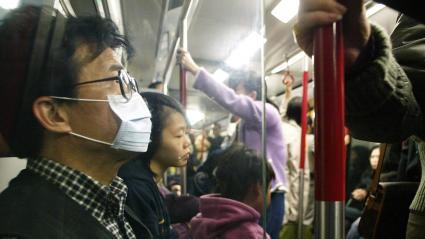 Une femme porte un masque dans le métro de Hong Kong (Chine), le 22 décembre 2003.