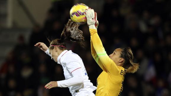 La gardienne de l'équipe de France, Sarah Bouhaddi (en jaune), s'empare du ballon face à l'Américaine Tobin Heath, lors d'un match amical, le 8 février 2015 au stade du Moustoir de Lorient.