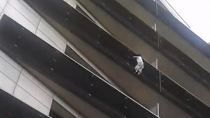 Sur cette capture d\'écran de la vidéo du sauvetage, on peut apercevoir le petit garçon s\'aider de ses pieds et du grillage pour se maintenir.