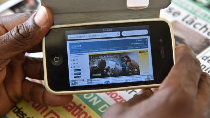 Un homme consulte son compte bancaire à partir de son smartphone le 24 avril 2015 à Abidjan (Côte d\'Ivoire)