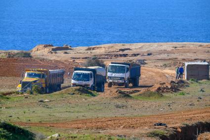 Noria decamions quise relaient toute la journee pour prélever le sable sur la côte atlantique du Maroc entre Asilah et Larache le 14 janvier 2019.