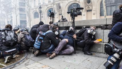 """Des journalistes s\'abritentsur les Champs-Elysées, le 8 décembre 2018, à Paris, pendant la manifestation des \""""gilets jaunes\""""."""