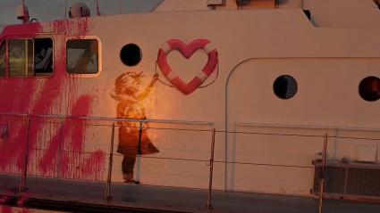 """Le graffiti de Banksy réalisé sur le navire \""""Louise Michel\"""", montrant une petite fille en gilet de sauvetage brandissant une bouée en forme de coeur."""