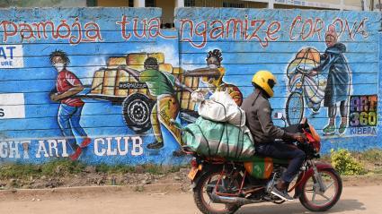 """Un motard passe devantungraffiti sur un mur deKibera, le plus grand bidonville de Nairobi, la capitale kényane,vsur lequel on peut lire \""""Pamoja tuangamize Corona\"""", qui signifie :\""""Combattons le corona ensemble\""""(13 août 2020)."""
